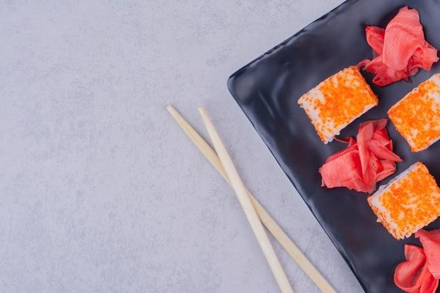 Rolos de salmão da filadélfia com gengibre vermelho em uma travessa de cerâmica