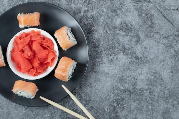 Rolos de salmão em uma travessa preta com gengibre vermelho marinado.