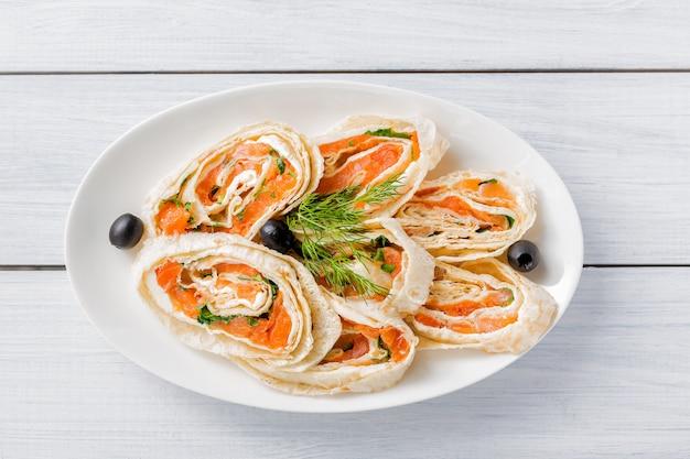 Rolos de salmão lavash com endro, queijo e azeitonas pretas na chapa branca e mesa de madeira