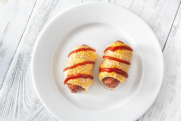 Rolos de salsicha no prato branco