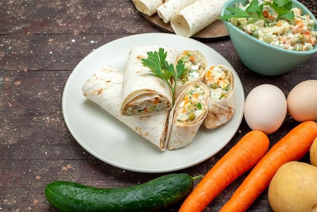 Rolos de sanduíche lavash de vista frontal fatiados com salada e carne dentro junto com salada e vegetais na madeira