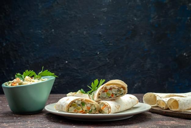 Rolos de sanduíche lavash de vista frontal fatiados com salada e carne dentro junto com salada em marrom