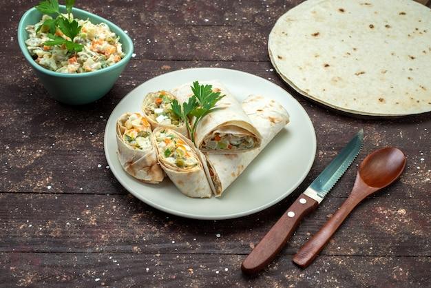 Rolos de sanduíche lavash de vista frontal fatiados com salada e carne dentro, junto com salada mayyonaise em prato branco sobre marrom