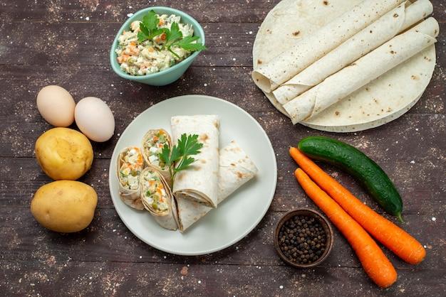 Rolos de sanduíche lavash fatiados com salada e carne dentro junto com salada mayyonaise no sanduíche de lanche da mesa de madeira