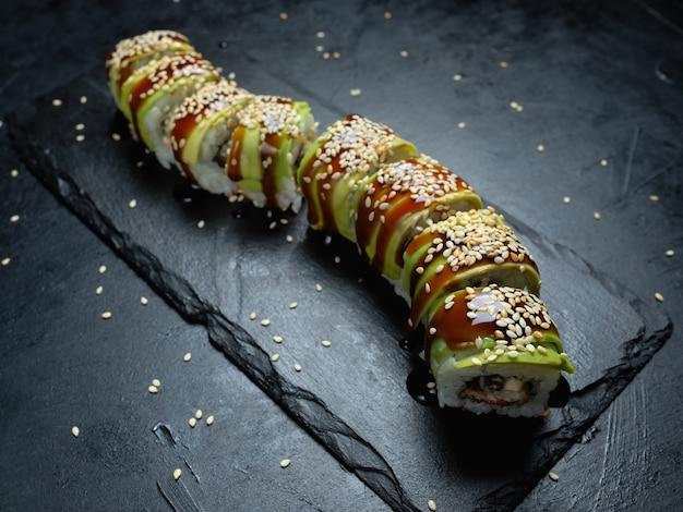 Rolos de sushi abacate dragão verde em fundo escuro. arte criativa da fotografia de alimentos. refeição culinária japonesa