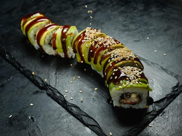 Rolos de sushi abacate dragão verde em fundo escuro com sementes de gergelim polvilhadas de cima. arte criativa da fotografia de alimentos.