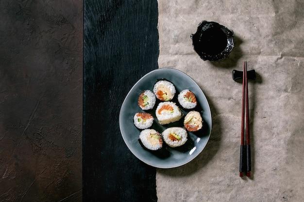 Rolos de sushi caseiro com salmão, omelete japonesa, avacado e molho de soja com pauzinhos de madeira no papel sobre o fundo de textura escura vista superior, plana leiga. jantar de estilo japonês. copie o espaço