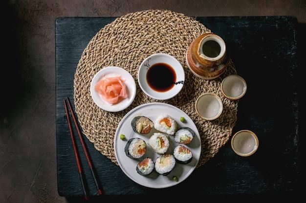 Rolos de sushi caseiro com salmão, omelete japonesa, avacado, gengibre, molho de soja com pauzinhos no guardanapo de palha na mesa de madeira preta. conjunto de saquê de cerâmica. vista superior, configuração plana. jantar estilo japonês