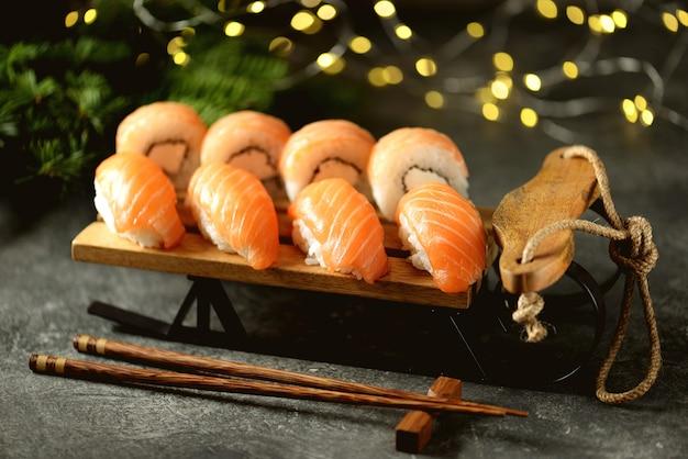 Rolos de sushi caseiro da filadélfia e sushi nigiri com salmão selvagem no trenó decorativo