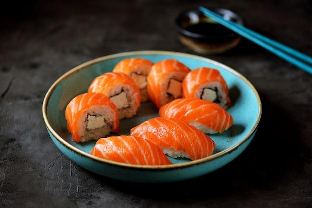 Rolos de sushi caseiro filadélfia e nigiri em uma placa azul sobre uma superfície preta.