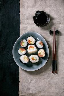 Rolos de sushi caseiros com salmão, omelete japonesa, avacado e molho de soja com pauzinhos de madeira em papel cinza sobre a superfície de textura escura vista superior, plana leiga. jantar estilo japonês