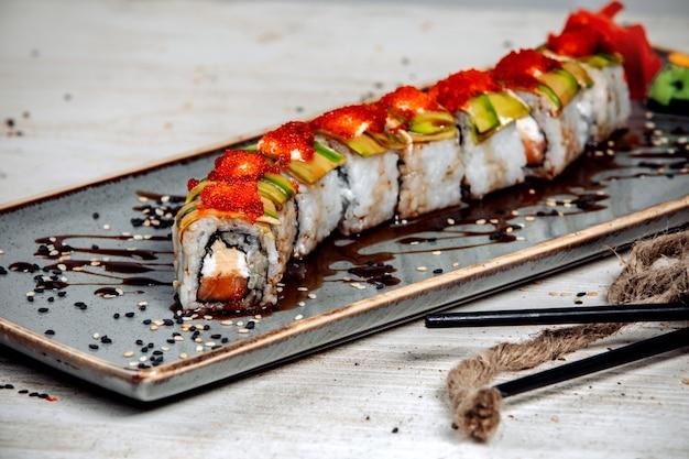 Rolos de sushi cobertos com abacate, creme e tobiko vermelho e molho de soja