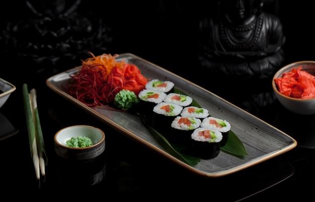 Rolos de sushi com aperitivos em um prato cinza