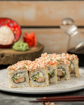 Rolos de sushi com camarão e pepino coberto com creme e tobiko vermelho