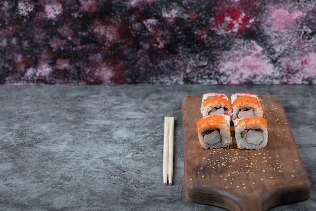 Rolos de sushi com caviar amarelo e vermelho em uma placa de madeira.