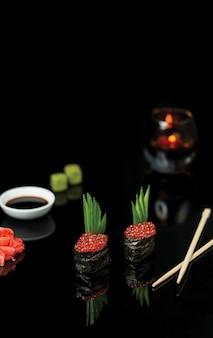 Rolos de sushi com caviar de salmão e molho.