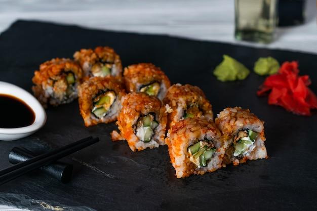 Rolos de sushi com caviar tobiko cheio de creme de queijo e pepino