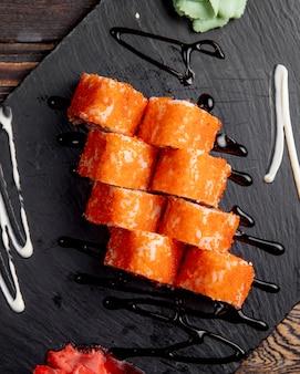 Rolos de sushi com caviar túbiko servido com gengibre e wasabi
