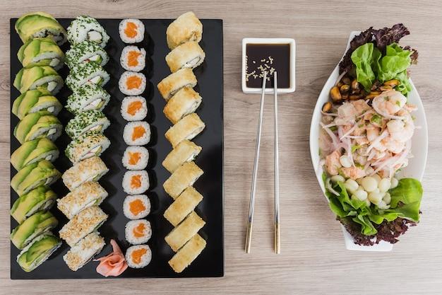 Rolos de sushi com ceviche e molho de soja em uma mesa de madeira