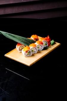 Rolos de sushi com folhas verdes em uma placa de madeira.