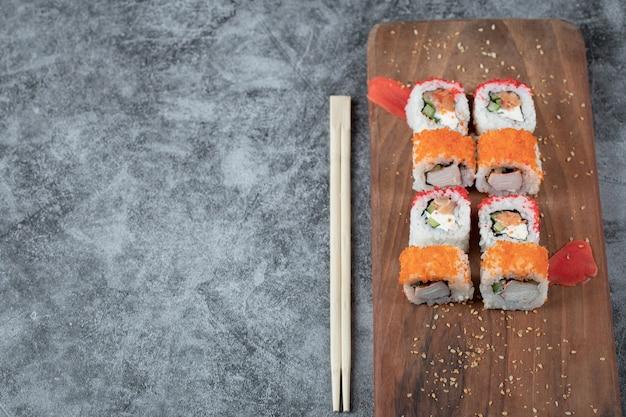 Rolos de sushi com frutos do mar e caviar vermelho isolado em uma travessa de madeira.