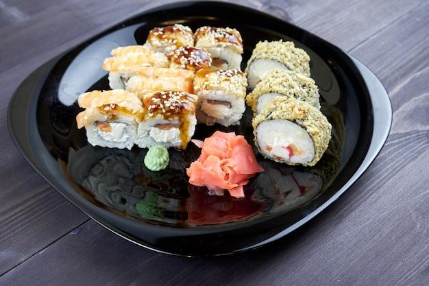 Rolos de sushi com gengibre e wasabi em uma placa preta