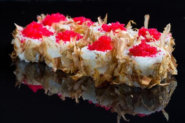 Rolos de sushi com lascas de atum ou salmão no preto.