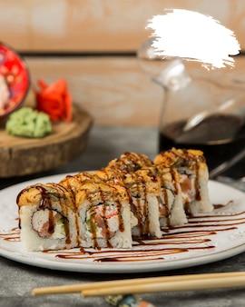 Rolos de sushi com molho de soja dentro da chapa branca.
