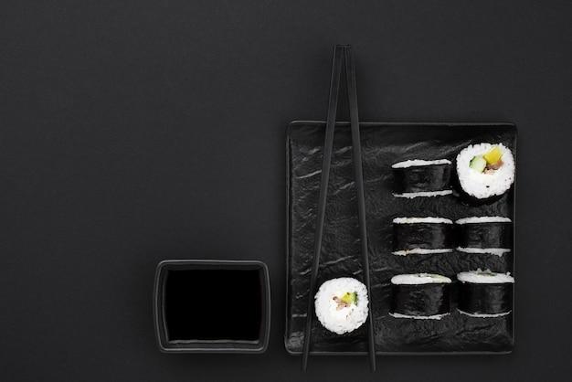Rolos de sushi com molho e espaço para texto