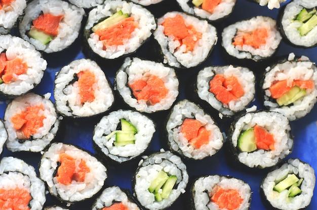 Rolos de sushi com o peixe vermelho salmão e pepino