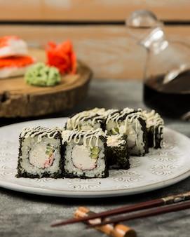 Rolos de sushi com palitos de caranguejo e pepino coberto com tobiko preto