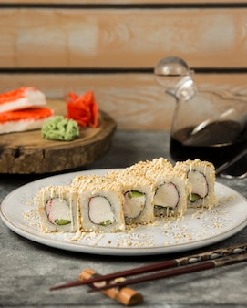 Rolos de sushi com palitos de caranguejo e pepino coberto de gergelim