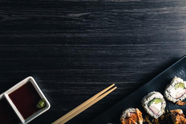 Rolos de sushi com pauzinhos e molho de soja no fundo escuro. copyspace e vista superior