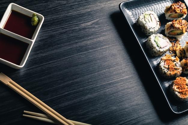 Rolos de sushi com pauzinhos e molho de soja no fundo escuro. espaço da cópia