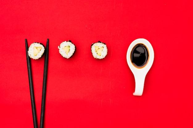 Rolos de sushi com pauzinhos e molho de soja sobre fundo vermelho