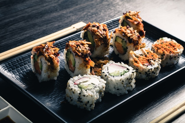 Rolos de sushi com pauzinhos na mesa de madeira escura