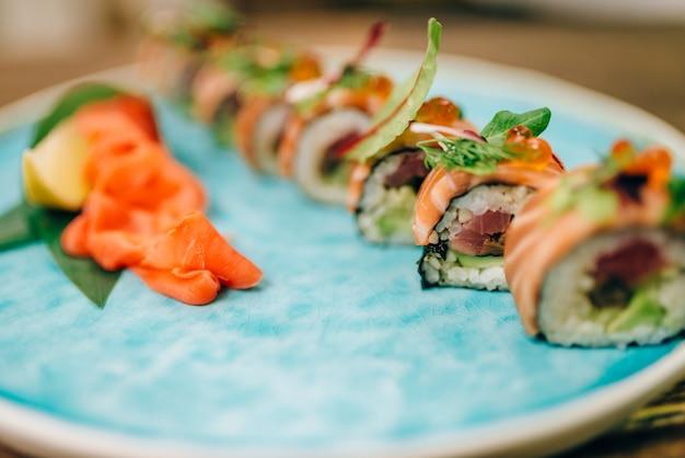 Rolos de sushi com peixe salmão na placa closeup.
