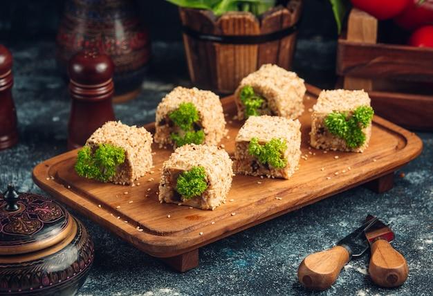Rolos de sushi com pistache verde em uma placa de madeira.