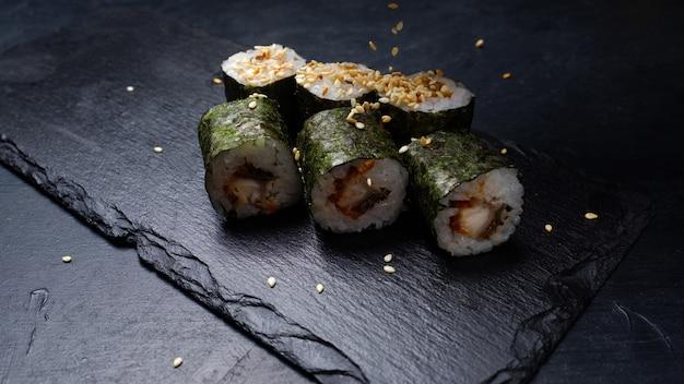 Rolos de sushi com salmão coberto de nori em fundo escuro. sementes de gergelim polvilhadas por cima. arte fotográfica de comida
