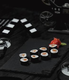 Rolos de sushi com salmão defumado na mesa escura.