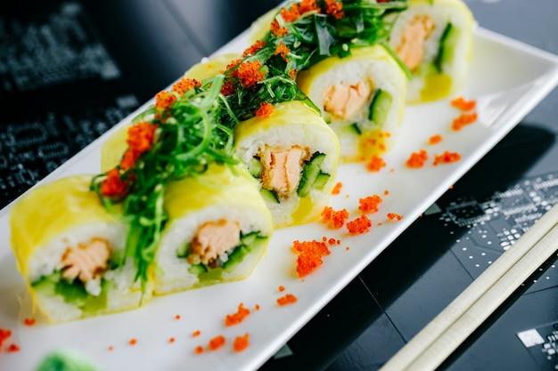 Rolos de sushi com salmão frito e pepino coberto com algas