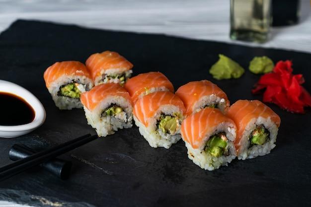 Rolos de sushi com salmão recheado com pepino e abacate cream cheese