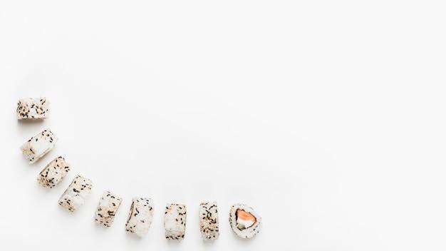 Rolos de sushi com sementes de gergelim, isoladas no fundo branco