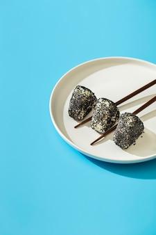 Rolos de sushi com sementes de gergelim no prato