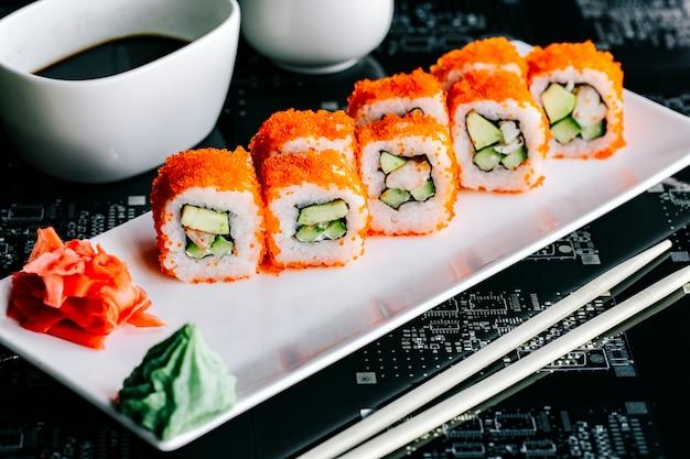 Rolos de sushi com tempurá de abacate coberto com tobiko vermelho