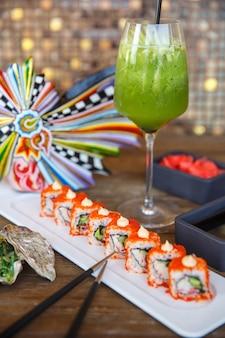 Rolos de sushi com tobiko vermelho servido com kiwi e coquetel de maçã verde