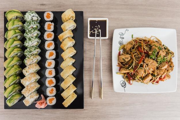 Rolos de sushi com yakisoba e molho de soja em uma mesa de madeira