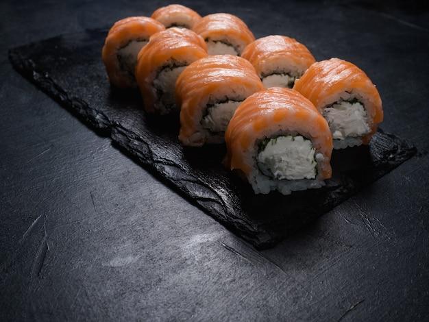 Rolos de sushi da filadélfia em fundo escuro. arte fotográfica de comida