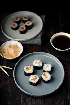 Rolos de sushi de alta vista em pratos e batatas fritas
