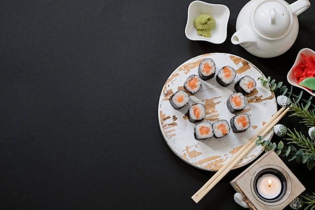 Rolos de sushi de comida japonesa de entrega de pedidos enquanto você fica em casa em quarentena. forma da casa em fundo preto, com espaço de cópia